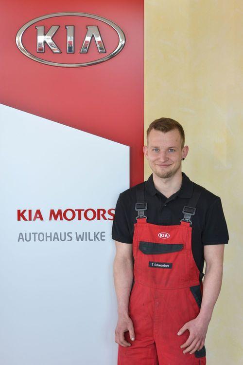 KFZ- Mechatroniker T.Schwamborn vor Kia Motors Logo Wand