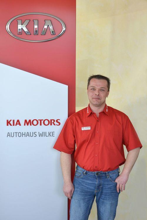 Annahmemeister Herbert Metzten vor Kia Motors Logo Wand