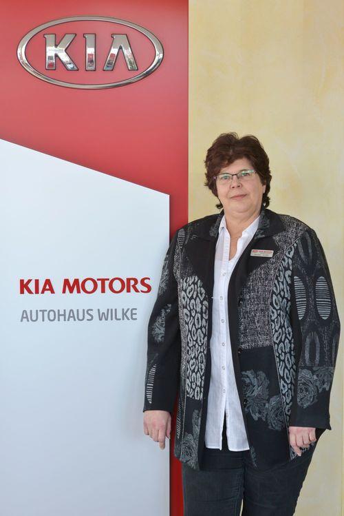 Buchhaltung Renate Wolter vor Kia Motors Logo Wand