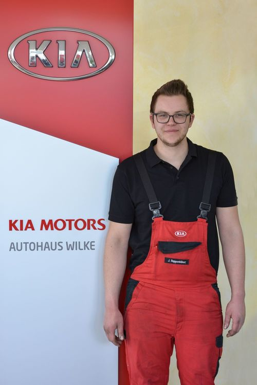 KFZ- Mechatroniker J.Rappenhöner vor Kia Motors Logo Wand
