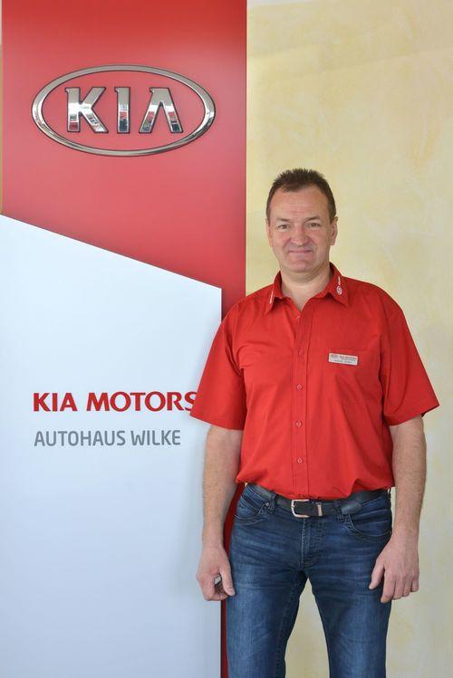 Inhaber Volker Wilke vor Kia Motors Logo Wand