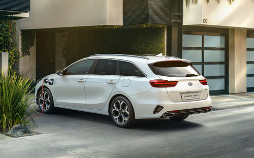 Kia Ceed SW PHEV in Weiss in Hauseinfahrt an Ladestation
