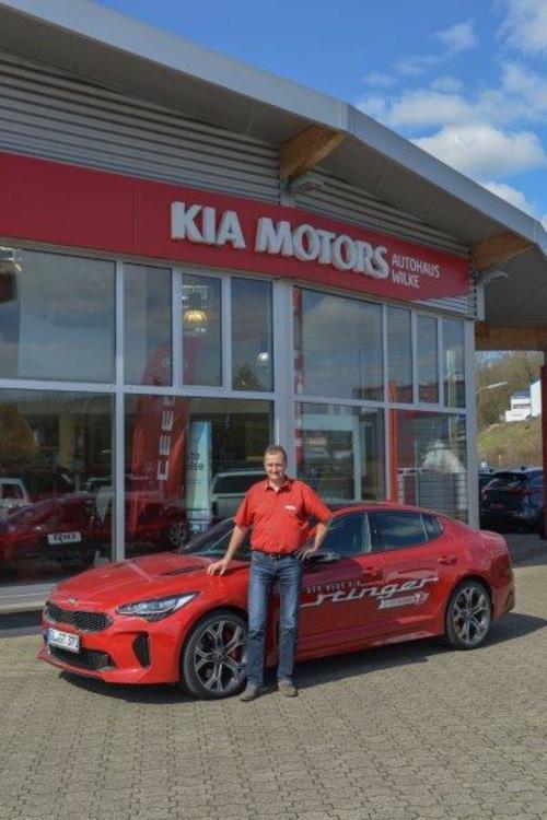 KIA Stinger in rot mit Autohaus Wilke Inhaber Volker Wilke vor dem Autohaus