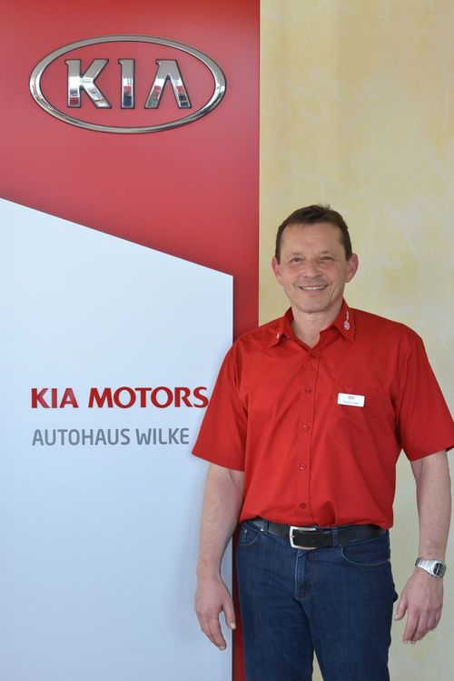 Verkäufer Thomas Lüsgen vor Kia Motors Logo Wand