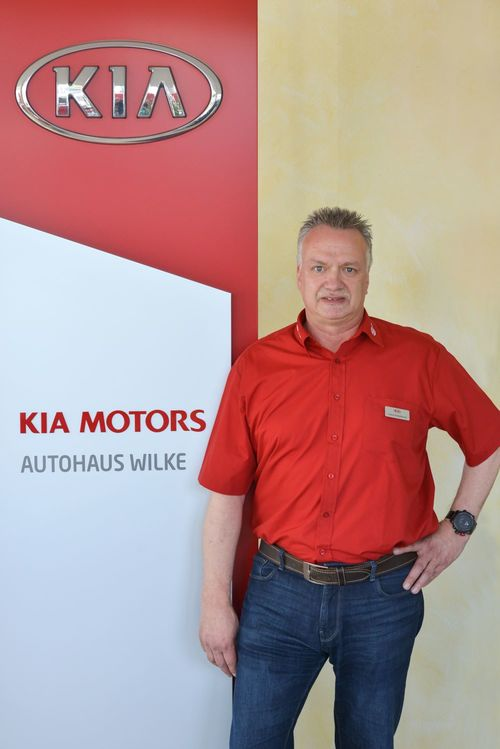 Frank Zweipfennig vor Kia Motors Logo Wand