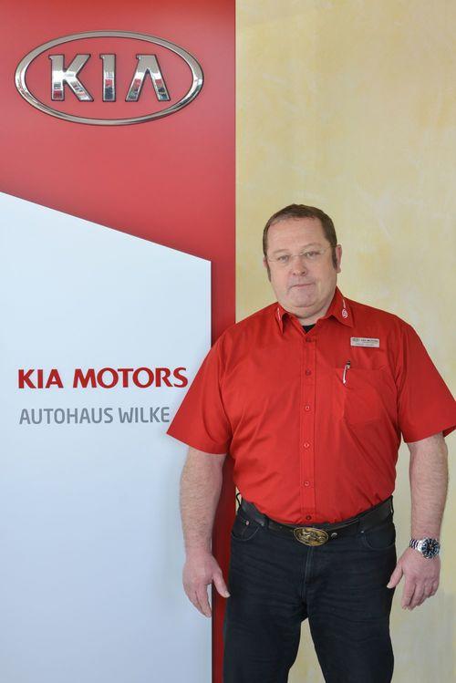 Annahmemeister Bernd Jordan vor Kia Motors Logo Wand