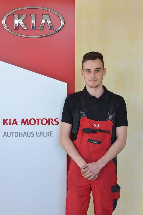 Azubi KFZ- Mechatroniker D.Knak vor Kia Motors Logo Wand