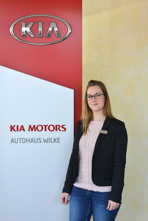 Terminvergabe Dana Scholtis vor Kia Motors Logo Wand