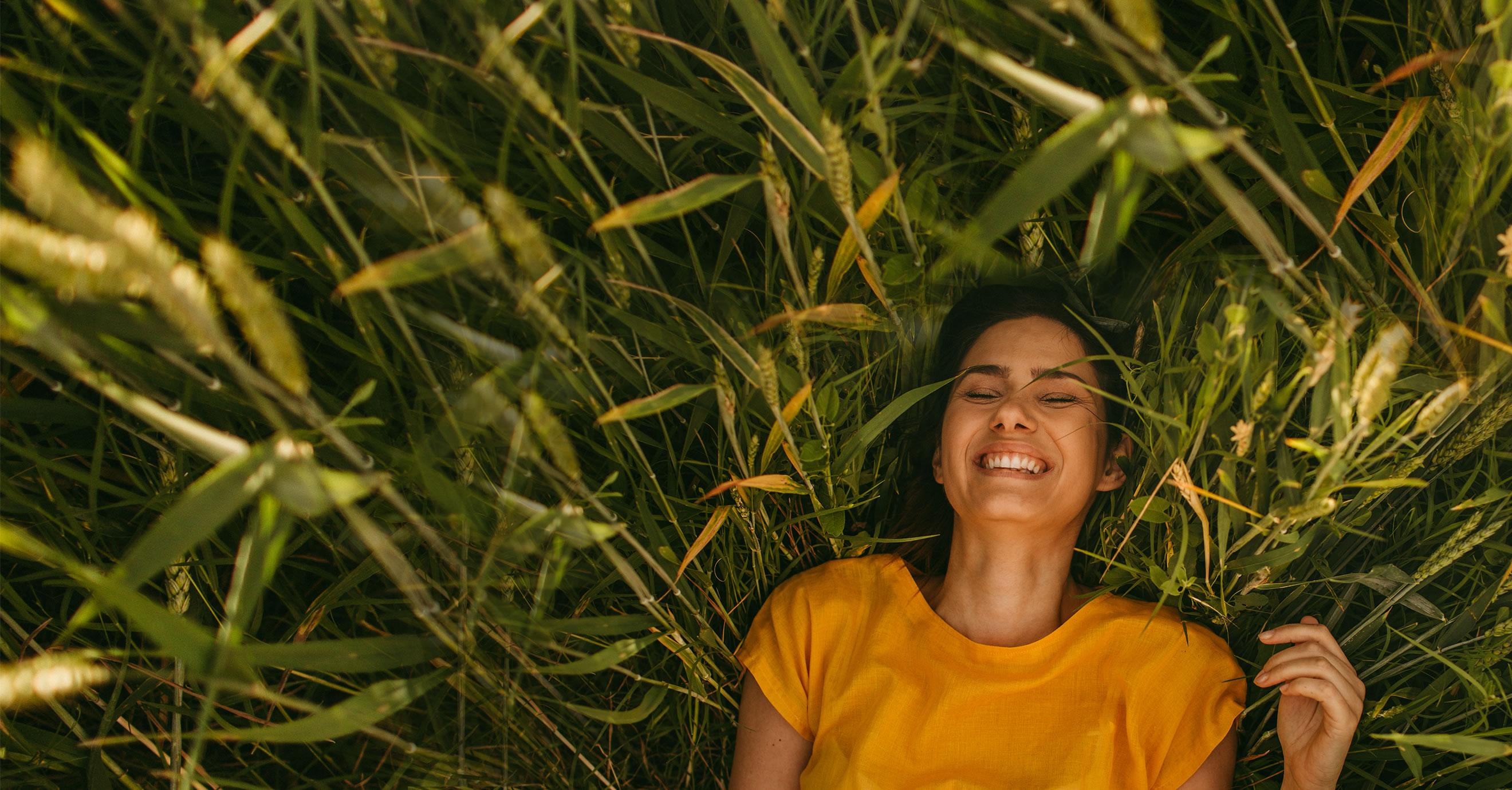 Bild liegende Frau im Gras von oben