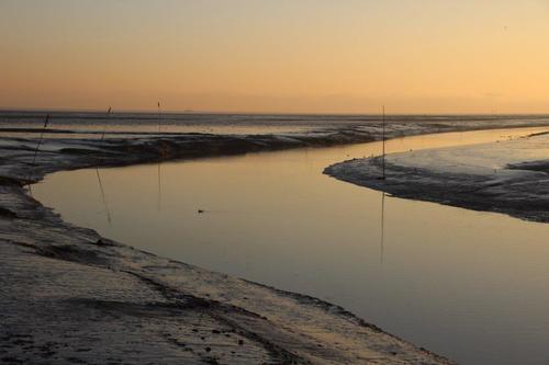 winterlicher Priel vor Sonnenaufgang. Erleben Sie einen Winterurlaub an der Nordseeküste im Hotel Leuchtfeuer Horumersiel.