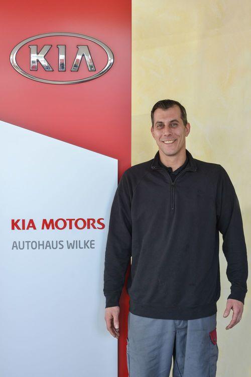 KFZ- Mechatroniker Daniel Dieper vor Kia Motors Logo Wand